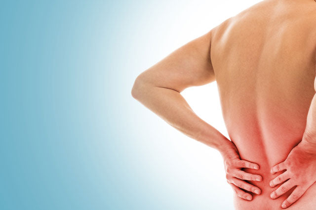 Shirtless man with hands on lower back due to pain