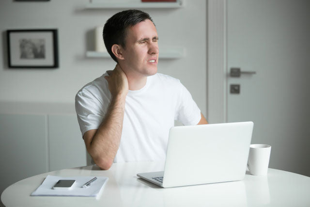 Man sitting at a desk using laptop with his hand on his neck and unhappy face due to pain