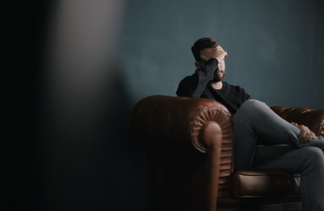 Man sitting on brown leather couch with hand on head