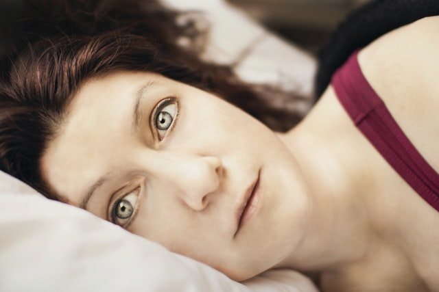 Woman with green eyes lying on her side in bed