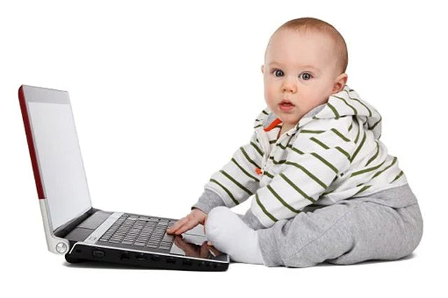 Baby boy sitting in front of computer