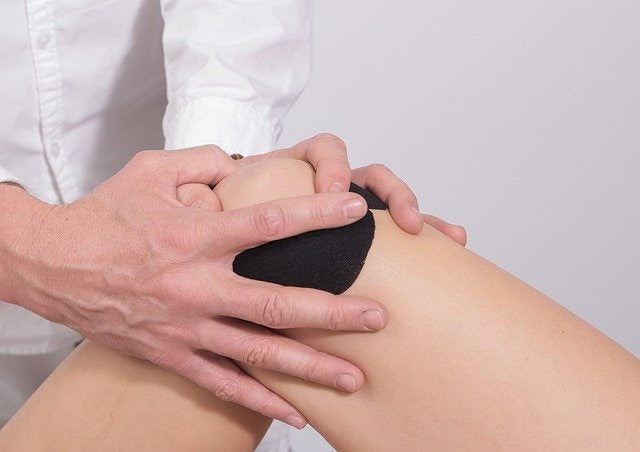 doctor's hands examining painful knee