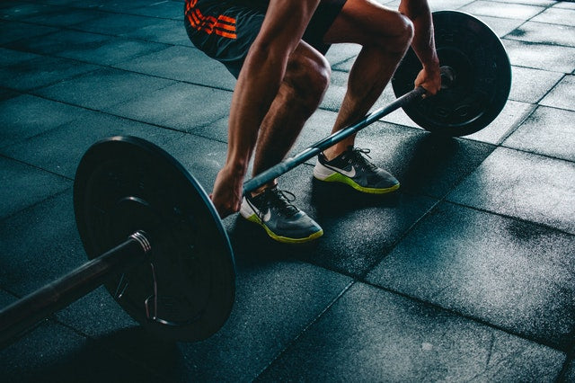 person gripping barbell in gym in squat position