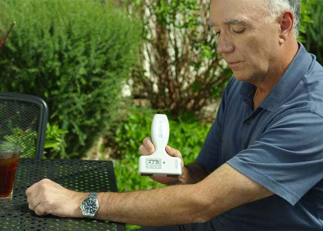 Man wearing watch using the SOLIS Pain Relief System