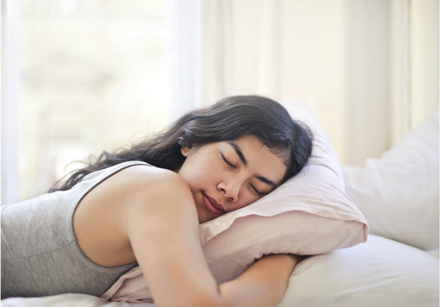 woman lying on her stomach, sleeping while hugging a pillow