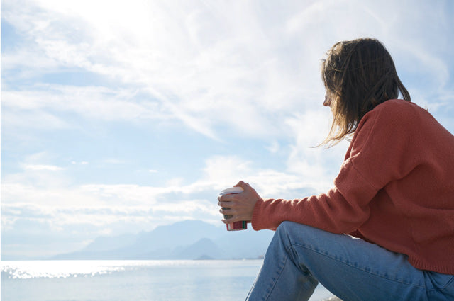 woman in jeans and orange sweater holding coffee looking at body of water