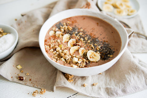 chocolate protein smoothie bowl with diced banana in background