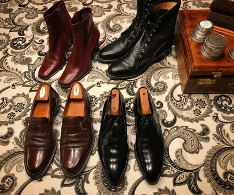 Flat lay of a shoe shine table - women's and men's boots, dress shoes, and loafers.