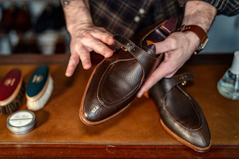 """Using your finger to buff or """"cross hatch"""" the dry cream evenly across the shoe"""