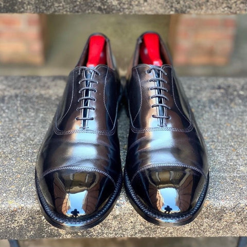 A pair of black cap toe calfskin oxfords mirror shined with Pure Polish High Shine
