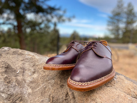 Pure Polish RAB Bespoke Oxblood Russian Hatch Grain Derbies on a rock with trees both shoes facing forward
