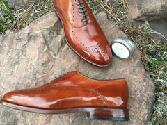 Pair of Mirror Shined Allen Edmonds Walnut Weybridge on a rock, with High Shine Paste reflecting in the toe