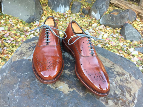 Lensing a Mirror Shined Pair of Allen Edmonds Weybridge on rocks with fall leaves in the background