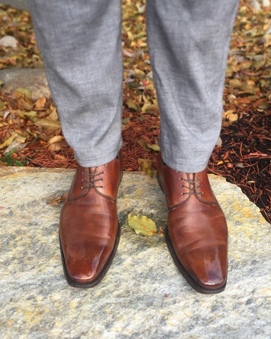 Men's Style Shot – Front shot of Brown Magnanni Derbies and Grey Agave Denim Slacks, Fall Leaves in the Background, Standing on a Flagstone