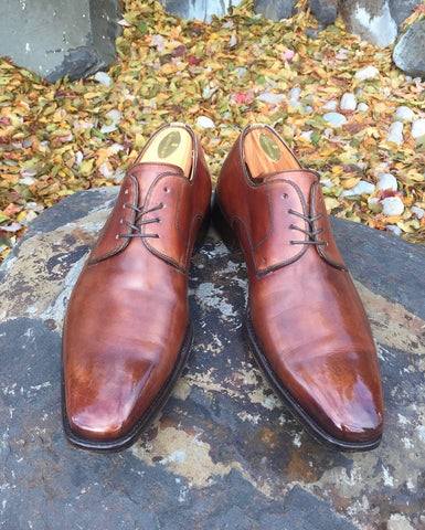 Light Brown Magnanni Colo Derby Shoes Mirror Shined on a Boulder in front of a pile of Autumn Leaves