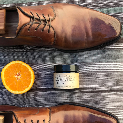 Orange slice next to a pair of polished leather derbies and a jar of Pure Polish