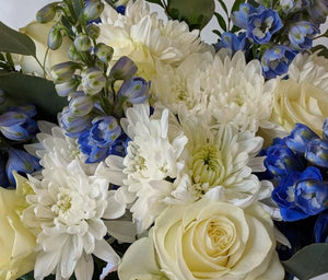 Blue delphinium flowers, white roses with fresh white flowers in handtied bouquet