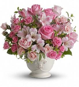 Pink flowers suitable for sympathy flowers, arranged in white container.