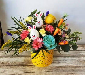 mixed flowers for easter in bright yellow container with fun accents available for free delivery in Winnipeg for easter.
