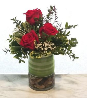 Broadway flowers include roses and greens in simple cylinder vase.