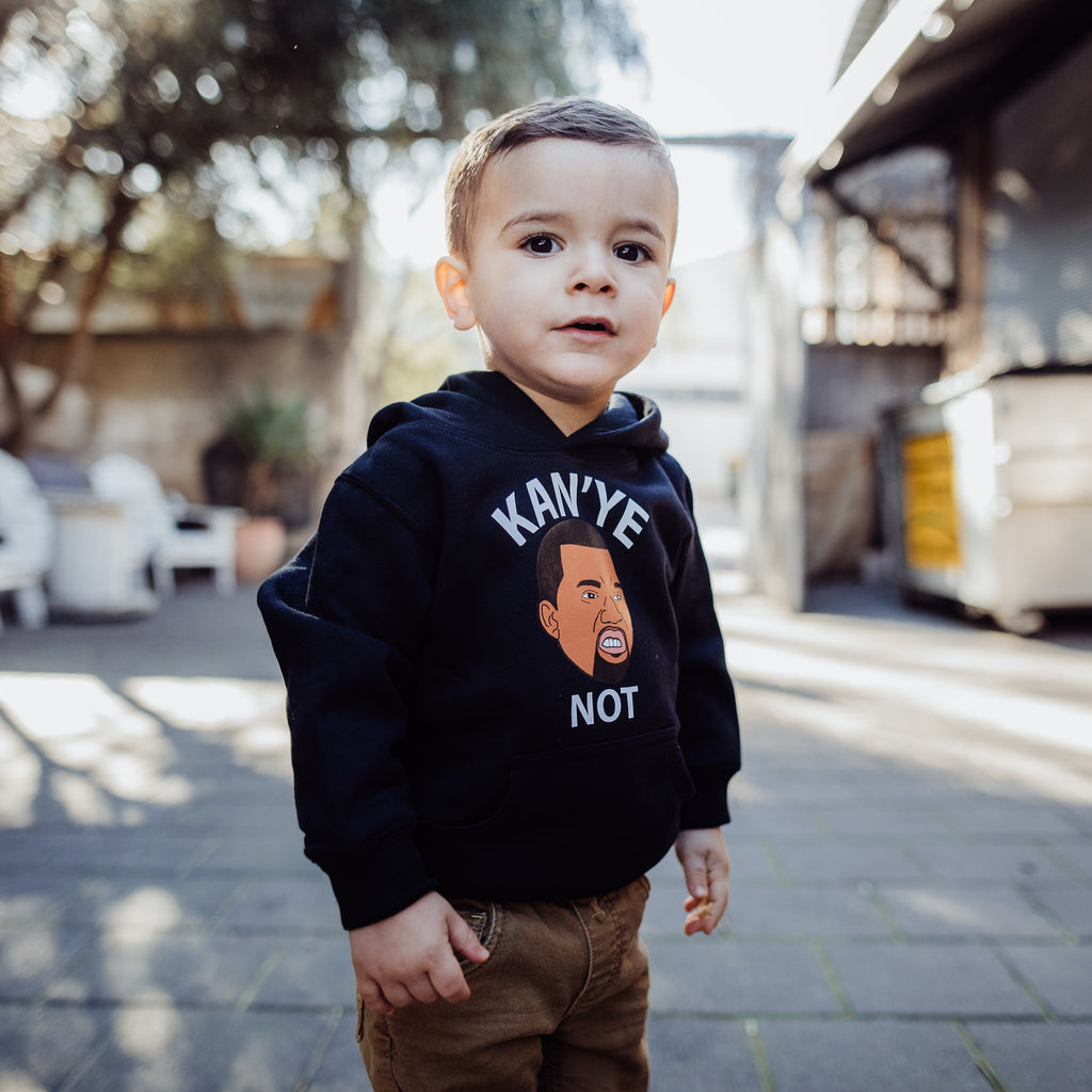 young boy child wearing Kanye hoodie in black and chinos looking towards camera