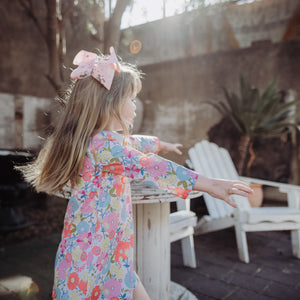 Young girl child in spring floral charlotte dress and bow in pink hair dancing in courtyard, white deck chairs in background