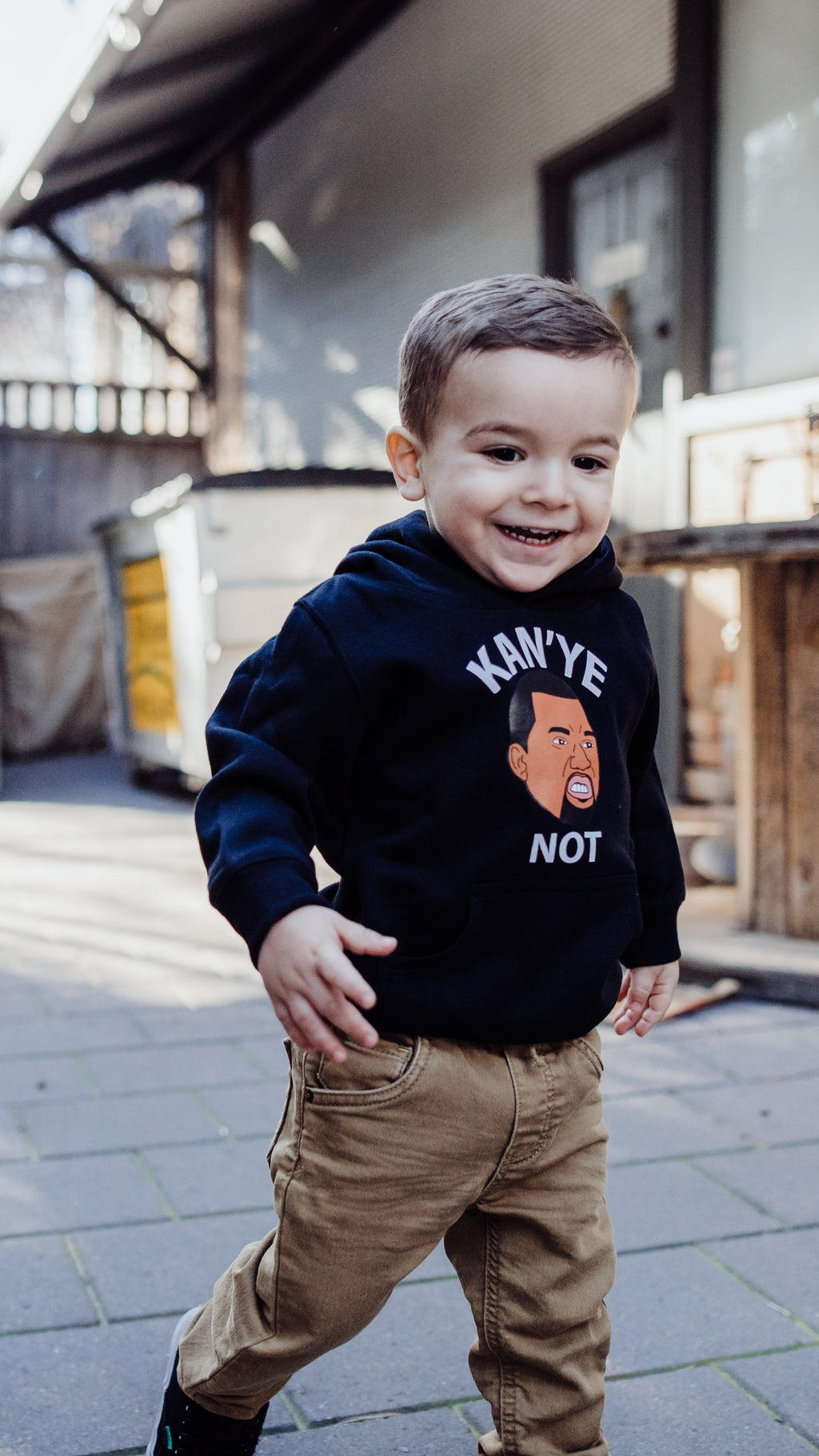 young boy child wearing Kanye hoodie in black and chinos running towards camera smiling