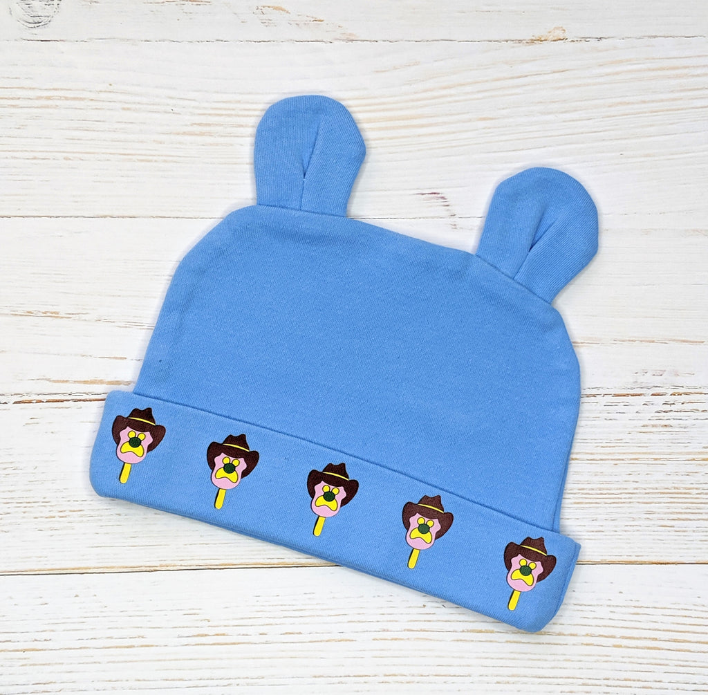 Blue Bubble O'Bill pattern beanie with bunny ears flatlay on wooden background
