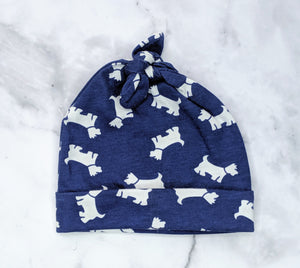 Handmade jersey beanie in a navy and white dog pattern flatlay on marble background