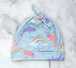 Handmade jersey beanie in a blue, pink & purple seal unicorn pattern flatlay on marble background