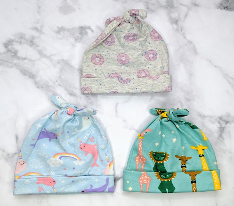 3 Handmade jersey beanies flatlay on marble background