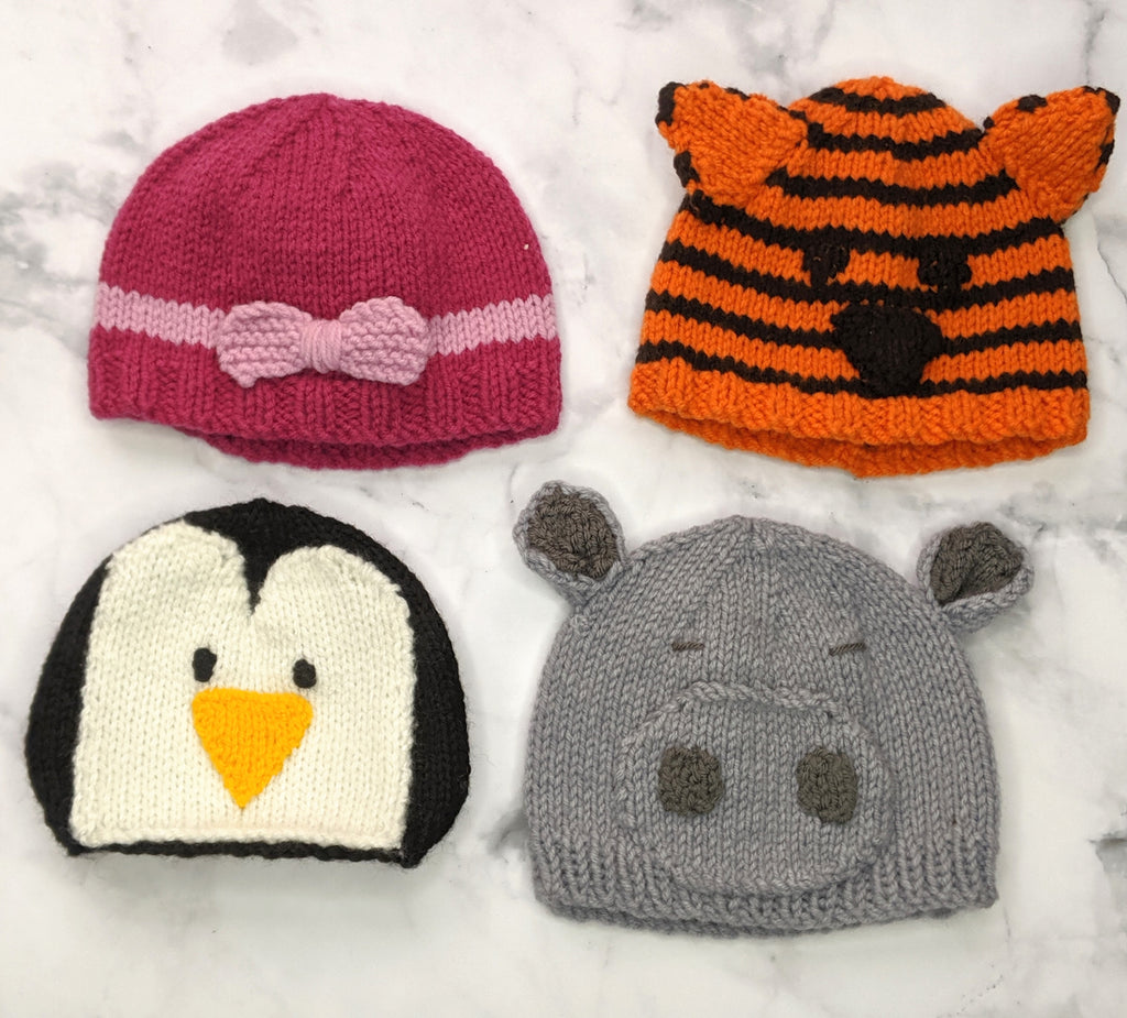 Various animal and coloured beanies on flatlay marble background
