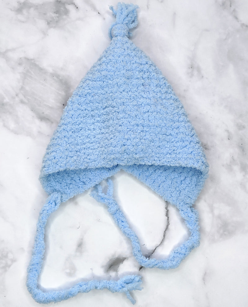 Handknit blue bonnet flatlay on marble background