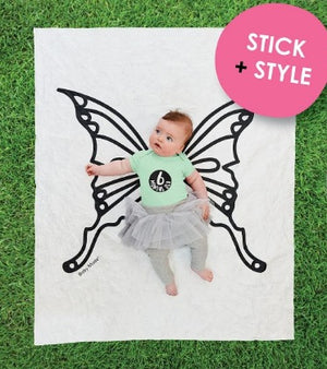 Baby lying on butterfuly backdrop over grass