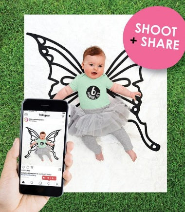 baby laying on the butterfly backdrop with adult hand holding a camera taking a photo of the baby
