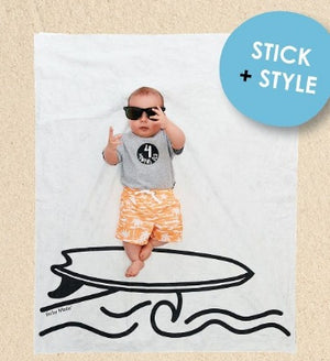 Baby lying on surfer backdrop over sand