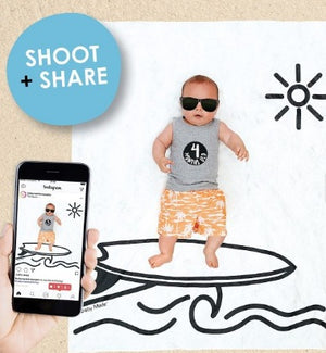 baby laying on the surfer backdrop with adult hand holding a camera taking a photo of the baby
