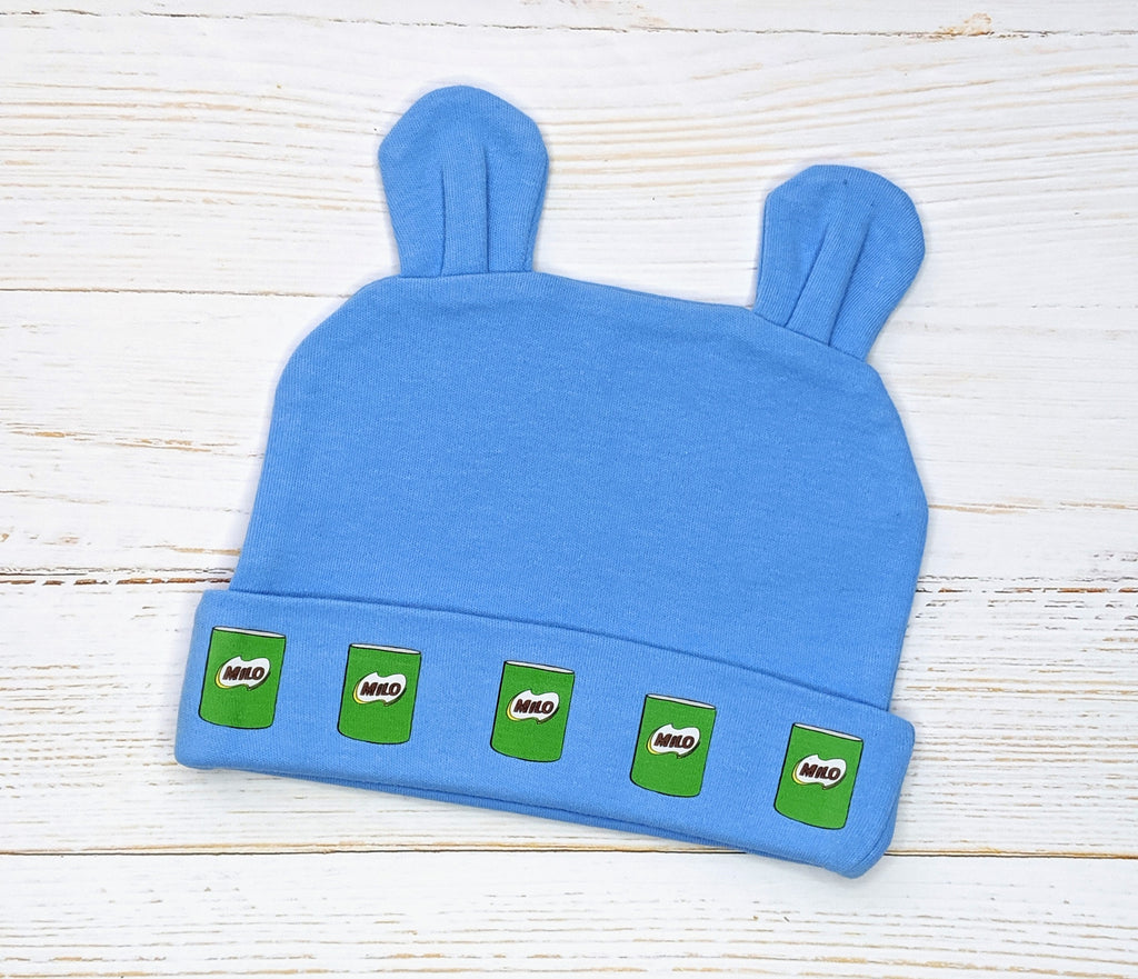 Blue Milo Cans pattern beanie with bunny ears flatlay on wooden background