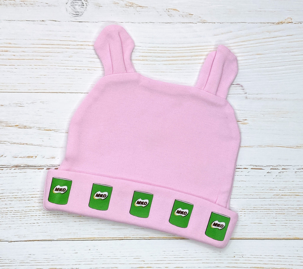 Pink Milo Cans pattern beanie with bunny ears flatlay on wooden background