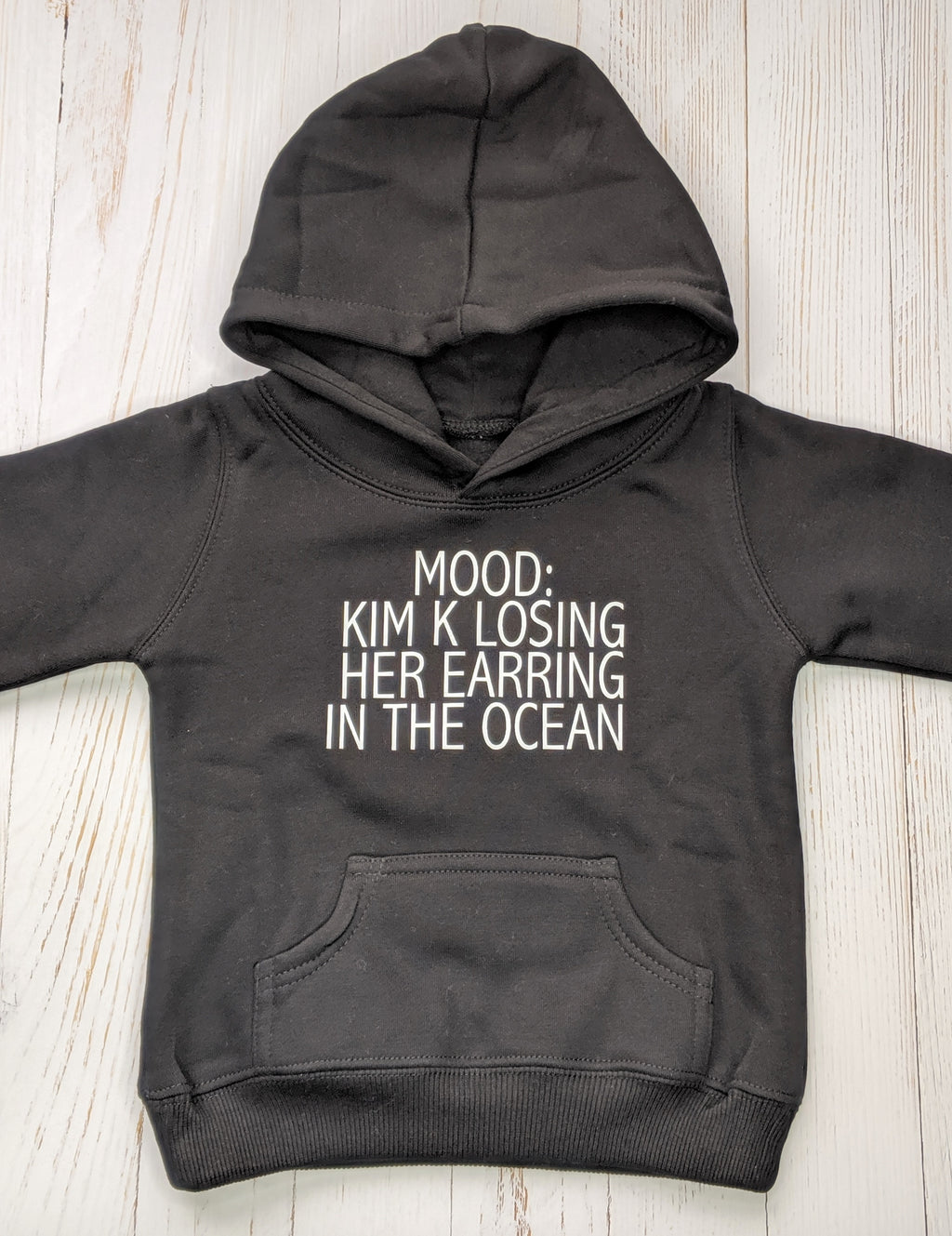 Black hoodie with 'mood: kim k losing her earring in the ocean' printed in white. flatlay on white wooden background
