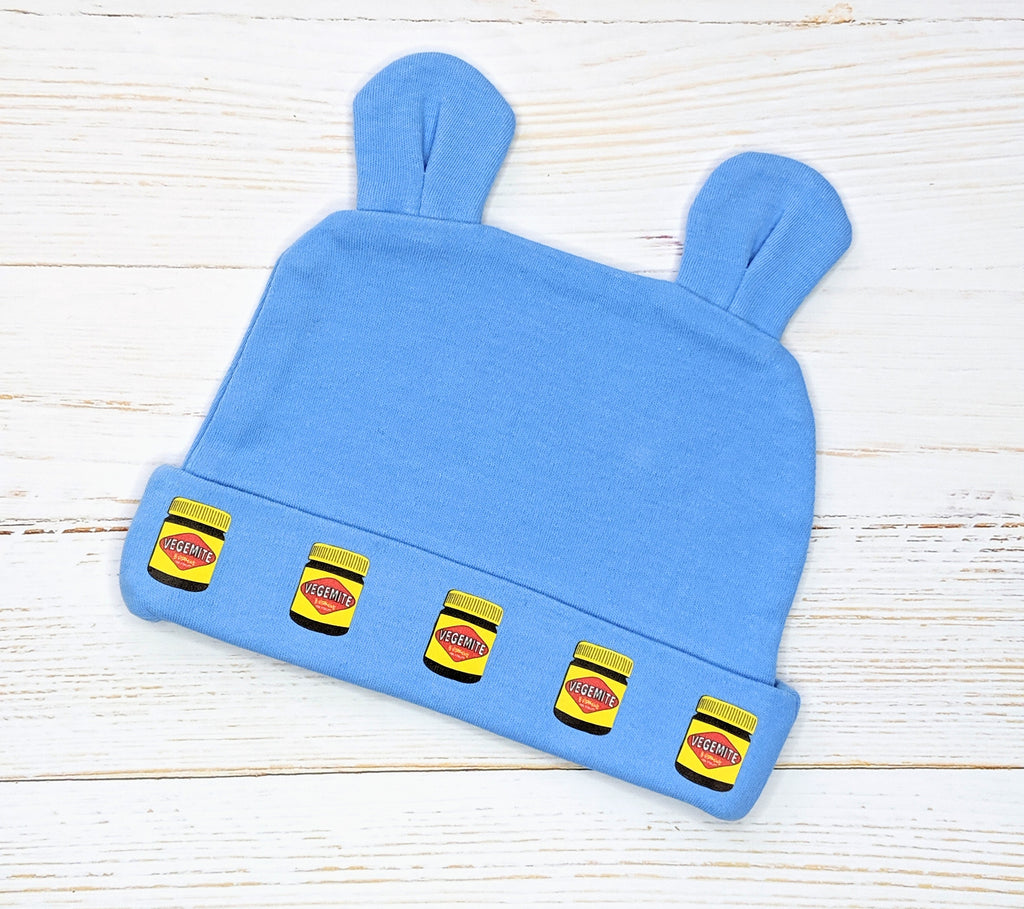 Blue Vegemite Jars pattern beanie with bunny ears flatlay on wooden background