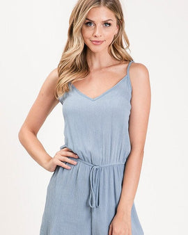 Textured solid color spaghetti strap jumpsuit with drawstring waist.