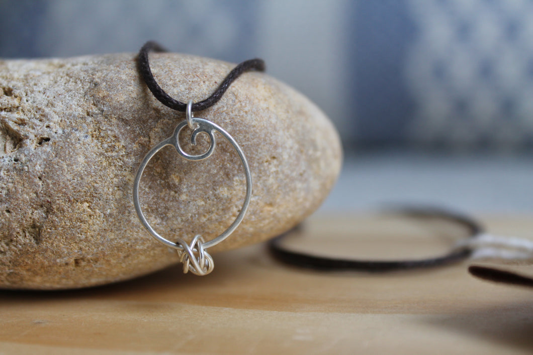 Spiralling flow necklace on brown cord