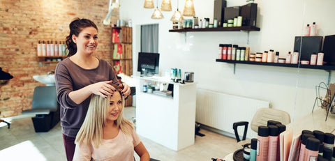 Stylist discussing hair with client in salon.