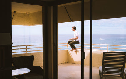 A man drinking coffee while sitting on the parapet of a modern windowed balcony, overlooking the ocean.