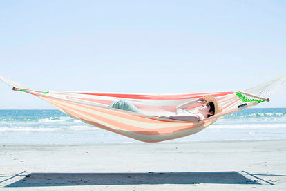 A woman, relaxing in a striped hammock, at the beach.