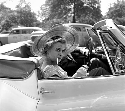 Black and white photograph of woman in the 50s, sitting in a white convertible, smoking a cigarette.
