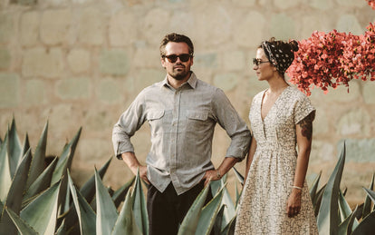 A couple standing in a garden, amongst agave plants, her looking at him looking into the distance, both wearing sunglasses.