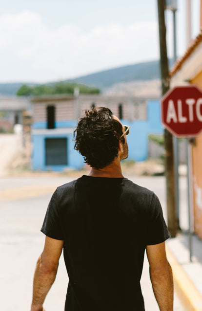 A guy in a black tee, walking towards a sign that reads 'ALTO'.