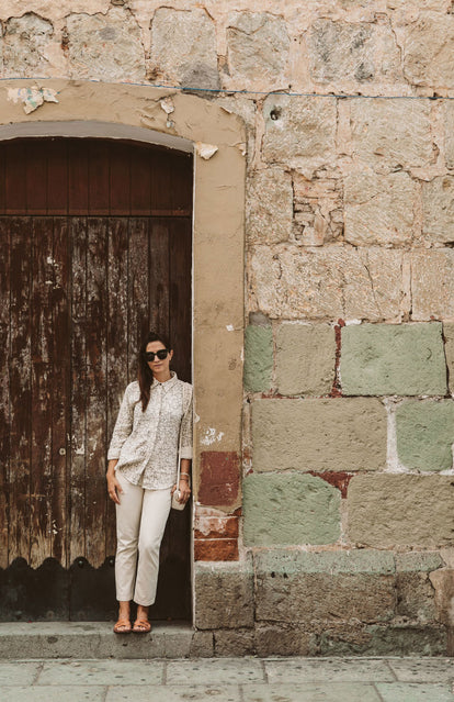A wona leaning against a large wooden door in a an oversized stone doorway.